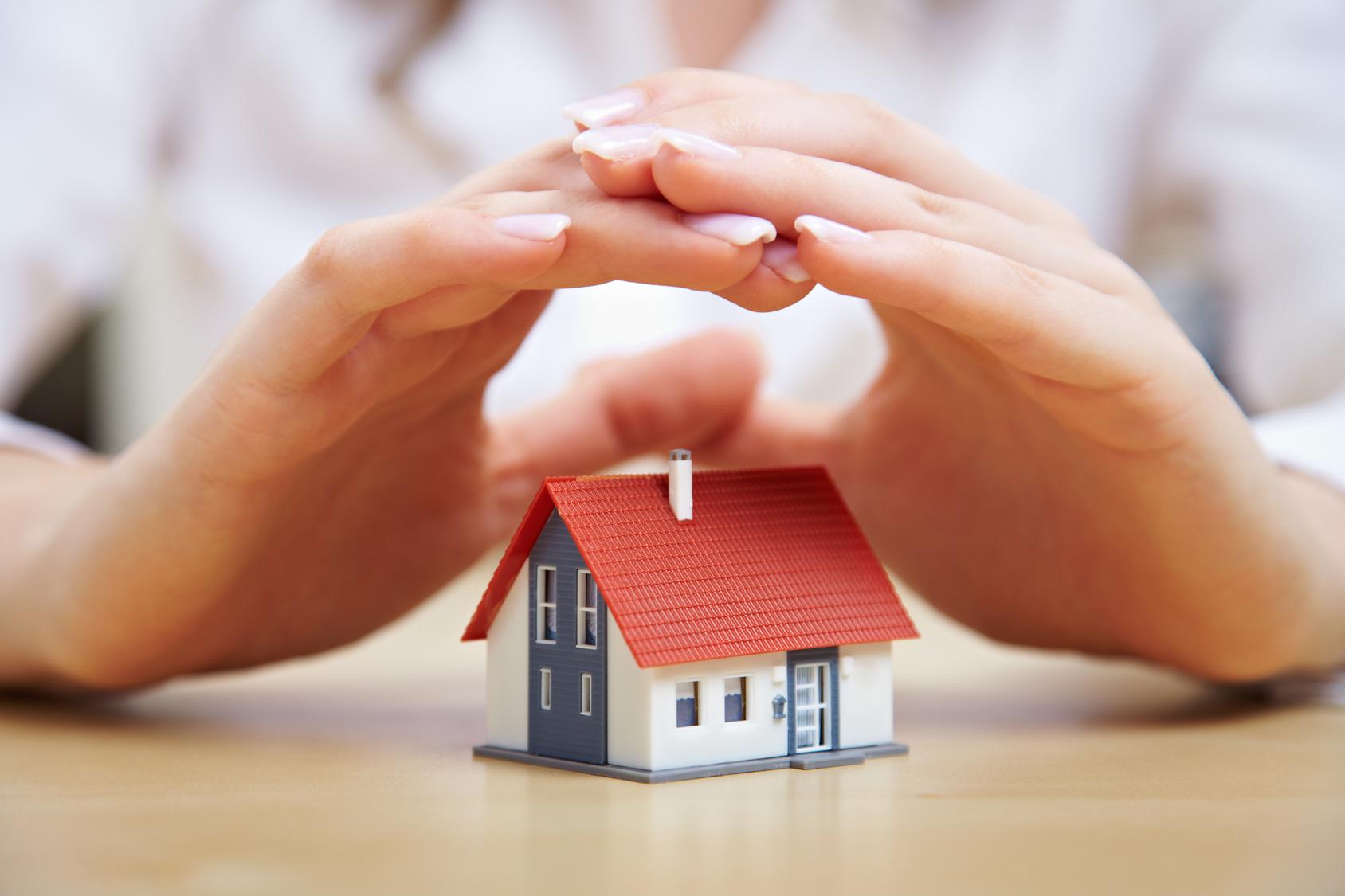 Weibliche Hände schützen ein kleines Einfamilienhaus